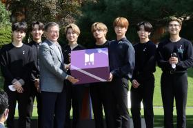 South Korean President Moon Jae-in and members of K-Pop boyband BTS pose for photographs with a gift given by BTS during Youth Day at the Presidential Blue House in Seoul, South Korea, September 19, 2020.