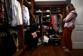 This photo taken on October 26, 2020, shows home organisers arranging the luxury wardrobe of client Chen Rui (R) in Beijing.
