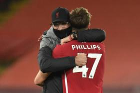 Juergen Klopp giving young centre-back Nat Phillips a hug after their 2-1 win over West Ham United earlier this month.