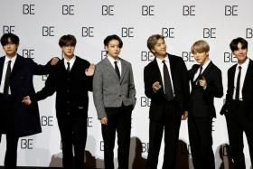 """Members of K-pop boy band BTS pose for photographs during a news conference promoting their new album """"BE(Deluxe Edition)"""" in Seoul, South Korea, November 20, 2020."""
