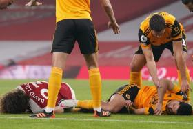 Arsenal defender David Luiz and Wolverhampton Wanderers striker Raul Jimenez (in orange) on the ground after a head-on collision in an EPL game last month.
