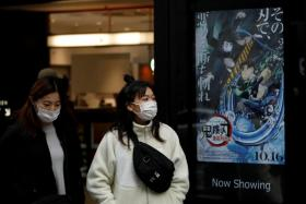 """Women wearing protective masks amid the coronavirus disease (COVID-19) outbreak walk past a poster for an animated movie """"Demon slayer"""" in front of a movie theatre in Tokyo, Japan, December 13, 2020."""
