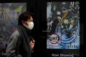 "A man wearing a protective mask amid the coronavirus disease (COVID-19) outbreak walks past a poster for an animated movie ""Demon slayer"" in front of a movie theatre in Tokyo, Japan, December 13, 2020."