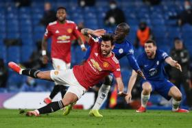 Manchester United midfielder Bruno Fernandes (in red) is shackled by Chelsea's N'Golo Kante.
