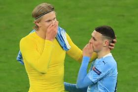 Borussia Dortmund's Erling Haaland (in yellow) having a chat with Manchester City's Phil Foden after their Champions League game.