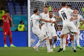 Italy's Lorenzo Insigne celebrates with teammates after scoring their third goal.