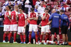 Denmark's players forming a protective wall around Christian Eriksen, who collapsed during their match against Finland.