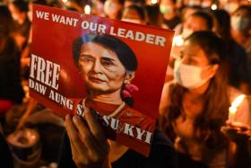 A Yangon protester holding a poster with an image of Myanmar's ousted leader Aung San Suu Kyi in March.