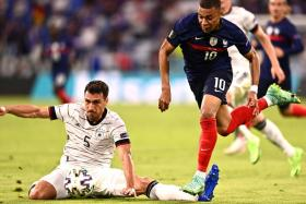France's Kylian Mbappe (right) gets challenged by Germany's Mats Hummels.