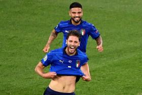 Manuel Locatelli (front) celebrates with Lorenzo Insigne after scoring Italy's first goal.