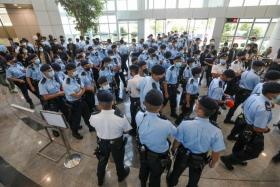 Police officers gathering at the headquarters of Apple Daily in Hong Kong.