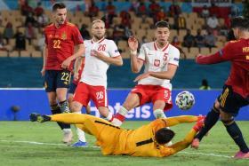 Poland goalkeeper Wojciech Szczesny (in yellow) attempting to deny Spain's Alvaro Morata (right).