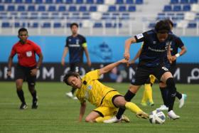Tampines midfielder Kyoga Nakamura (in yellow) vying for the ball with Gamba Osaka's Kosuke Onose.