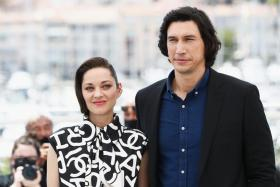 """US actor Adam Driver (R) and French actress Marion Cotillard pose during a photocall for the film """"Annette"""" at the 74th edition of the Cannes Film Festival in Cannes, southern France, on July 6, 2021."""