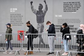 Members of the public queue to receive a dose of a Covid-19 vaccine outside a temporary vaccination centre set up a the Emirates Stadium, home to Arsenal football club, in north London on June 25.