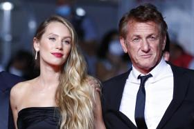"""US actor and director Sean Penn (R) and his daughter US actress Dylan Penn arrive for the screening of the film """"Flag Day"""" at the 74th edition of the Cannes Film Festival in Cannes, southern France, on July 10, 2021."""