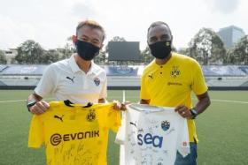 Lion City Sailors' chief executive Chew Chun-Liang exchanging jerseys with Suresh Letchmanan, managing director of BVB Asia Pacific.