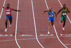 Italy's Lamont Marcell Jacobs (in blue) winning the Olympic men's 100m final. He was racing with an empty lane on his right after Britain's Zharnel Hughes was disqualified following a false start.