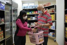 Sembawang GRC MP Mariam Jaafar helping resident Toh Kok Jin pick groceries at Store@Woodlands.