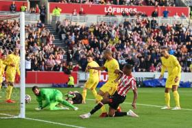 Brentford's Ethan Pinnock (in red and white stripes) scoring their first goal against Liverpool.