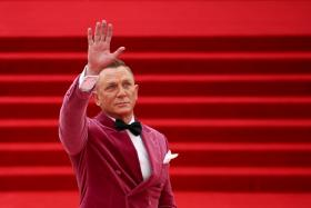 """Cast member Daniel Craig salutes as he arrives the world premiere of the new James Bond film """"No Time To Die"""" at the Royal Albert Hall in London, Britain, September 28, 2021."""
