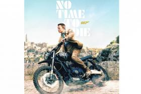 A No Time To Die film poster featuring Daniel Craig as James Bond riding the Triumph Scrambler 1200 XE.