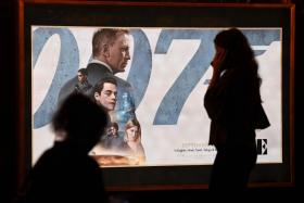 """A woman walks past a poster of the latest James Bond movie """"No Time to Die"""" at a cinema in New Delhi on September 30, 2021."""