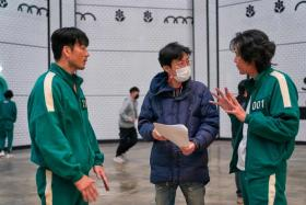 Director Hwang Dong-hyuk (centre) has seemingly relented on making a second season of the massively successful Netflix K-drama.