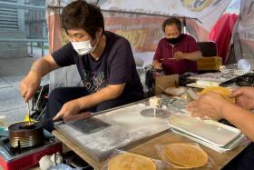 In this picture taken in Seoul on October 10, 2021, street vendors Jung Jung-soon (L) and her husband Lim Chang-joo (R) make dalgonas, a crisp sugar candy featured in the Netflix smash hit series Squid Game, for which they were hired to be on set to make during production.