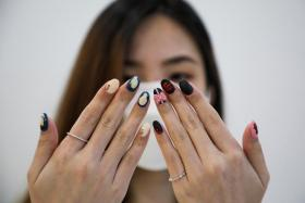 A customer shows her Squid Game's manicure at the nail salon Maniqure in Kuala Lumpur, Malaysia October 14, 2021.