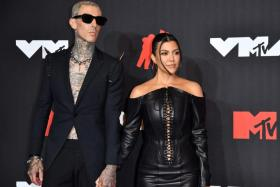 US drummer Travis Barker and US personality Kourtney Kardashian arrive for the 2021 MTV Video Music Awards at Barclays Center in Brooklyn, New York, September 12, 2021.