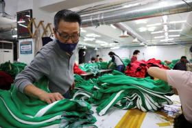 """Ko Jong-hyun, 59, a clothing factory owner, checks newly made tracksuits inspired by Netflix series """"Squid Game"""" at his plant in Seoul, South Korea, October 21, 2021."""