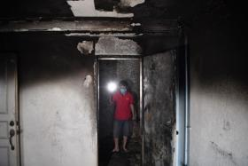 Mr Aung Myo Thant visits his home on Oct 21, 2021. His wife was in the flat with their three children when the fire occurred.