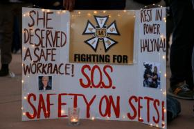 A woman displays a sign calling for workplace safety at a vigil for cinematographer Halyna Hutchins, who died after being shot by Alec Baldwin on the set of his movie Rust, in Albuquerque, New Mexico, U.S., October 23, 2021.