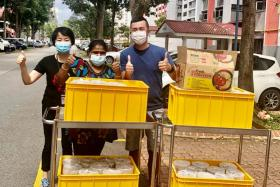 Mr Low Boon Chuan and volunteers during a delivery of fish porridge to senior activity centres and nursing homes.
