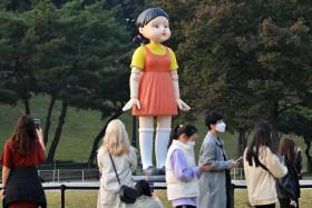 Squid Game's Younghee, a four-metre-tall doll dressed in orange and yellow, was set up at the Seoul Olympic Park.