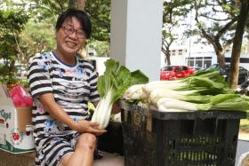 Madam Sandy Goh Siew Hua with baskets of vegetables she distributes as part of the food drive she runs.