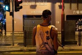 "A runner wearing a tank top with the slogan ""Hong Kong add oil"" walks on a street before the annual Hong Kong Marathon on Oct 24, 2021."