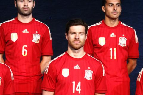 70b92dd96 Xabi Alonso (centre) and his team-mates model Spain s home kit for the 2014  World Cup. The reigning champions have been asked by Fifa to make a third  kit ...